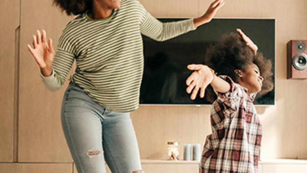 mother and daughter dancing in living room