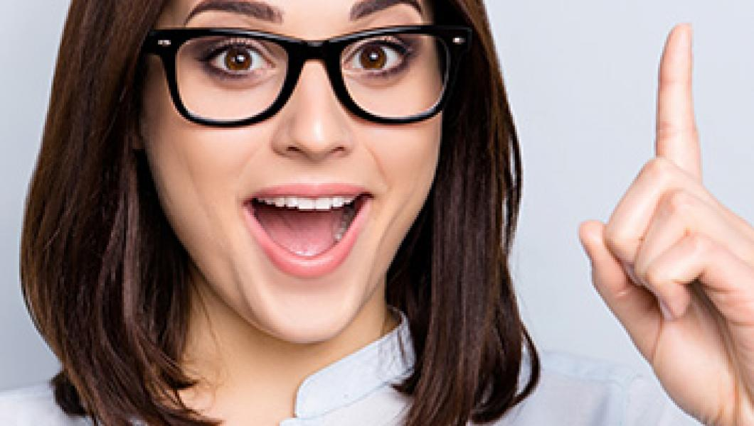 woman in glasses pointing her finger up