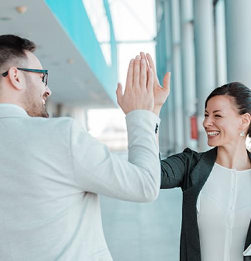 male and female businesspeople giving a high five