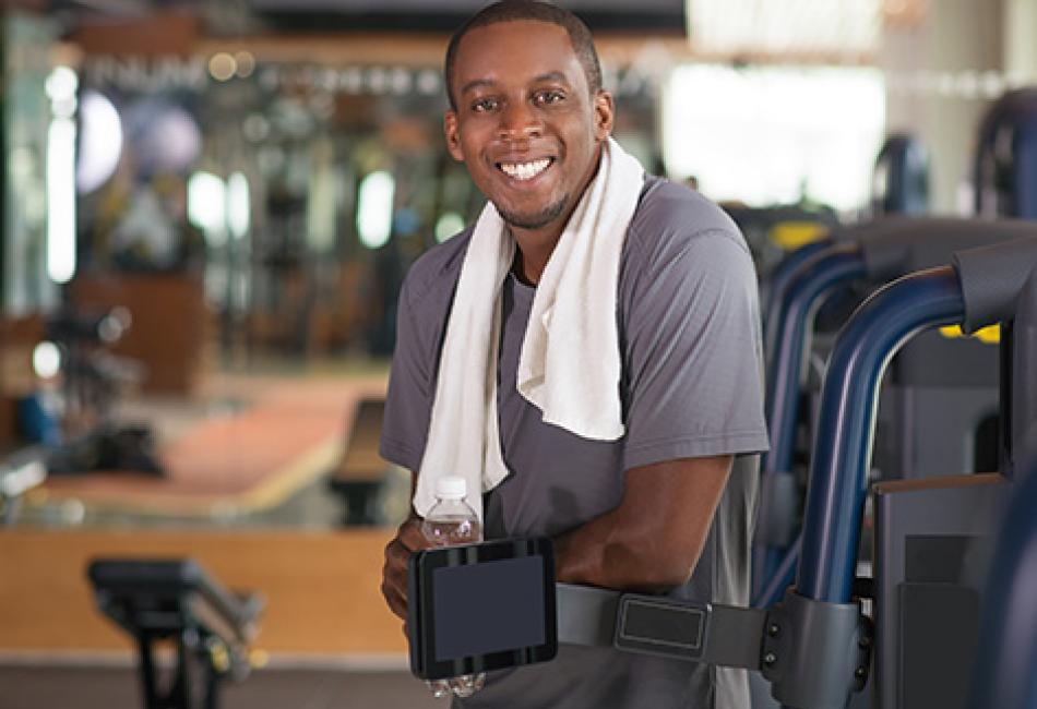 man at gym with leaning on exercise equipment smiling